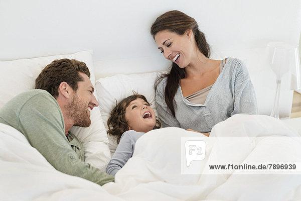 Eltern  die mit ihrem Sohn auf dem Bett spielen.