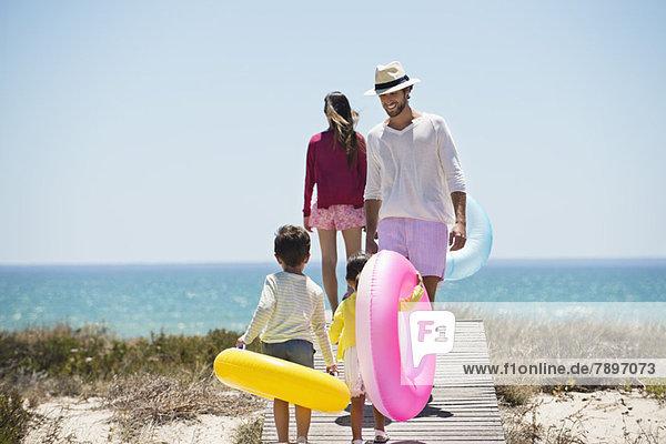 Kinder mit ihren Eltern halten aufblasbare Ringe an einer Strandpromenade.