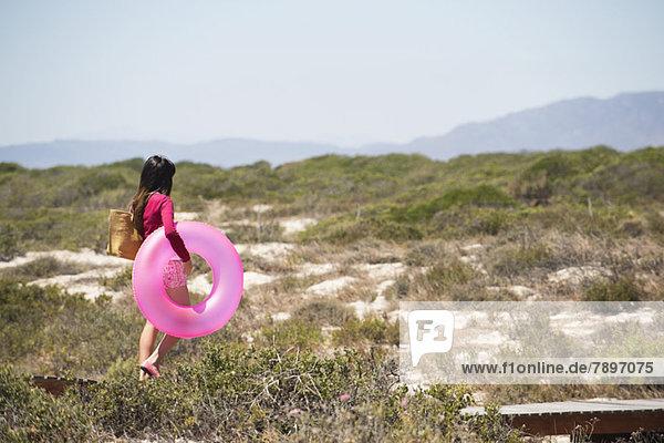 Frau hält einen aufblasbaren Ring und geht auf einer Strandpromenade spazieren.