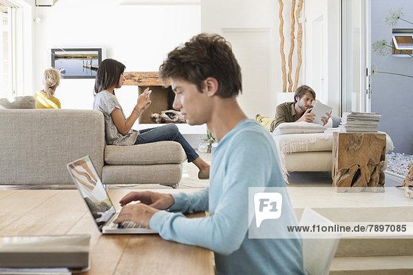 Mann mit einem Laptop und seinen Freunden mit elektronischen Gadgets im Hintergrund