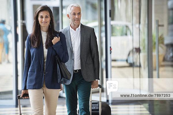 Geschäftsleute ziehen Koffer in einer Hotellobby