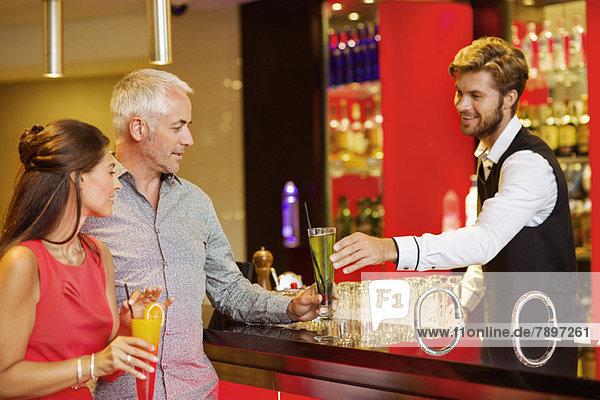 Barkeeper  der einem Paar an der Theke einen Drink serviert.