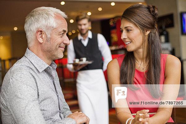 Paar lächelnd in einem Restaurant mit Kellner im Hintergrund