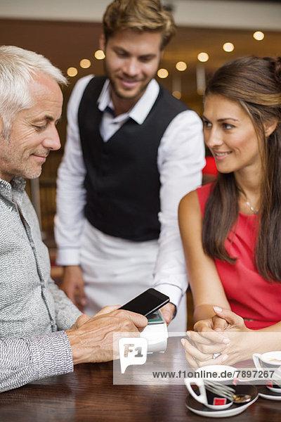 Kellner zeigt einem Paar auf einem Tisch in einem Restaurant ein Kreditkartenlesegerät. Kellner zeigt einem Paar auf einem Tisch in einem Restaurant ein Kreditkartenlesegerät.