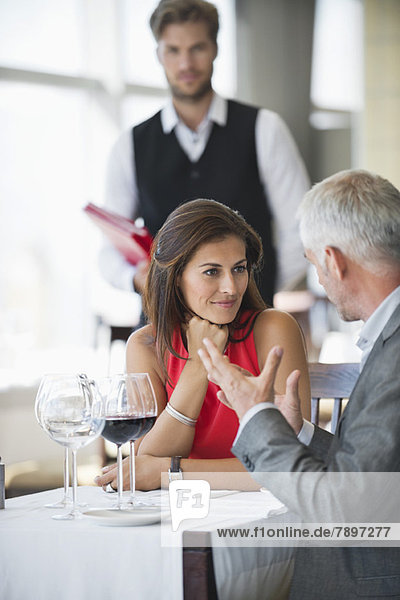 Couple discussing in a restaurant with waiter in the background
