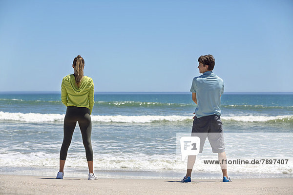 Rückansicht einer Frau und ihres Trainers beim Training am Strand
