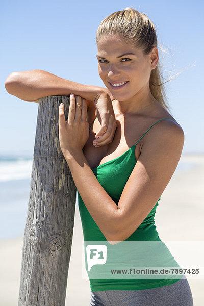 Lächelnde Frau  die sich an einen Holzpfosten am Strand lehnt.