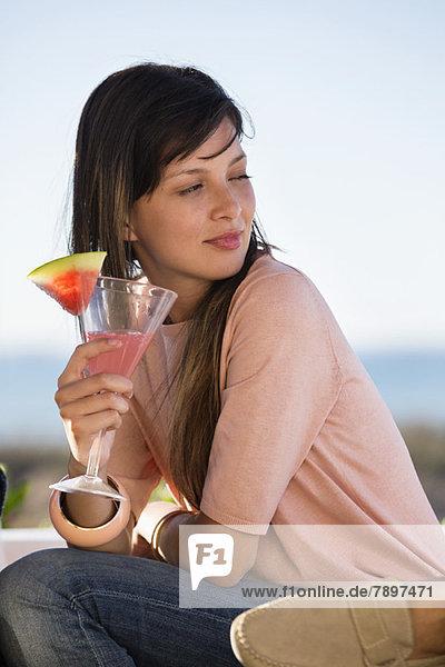 Frau trinkt Wassermelonen-Martini
