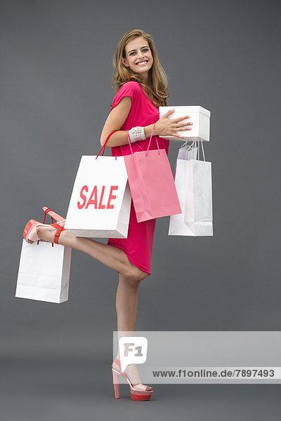 Porträt einer Frau  die mit Einkaufstaschen posiert und lächelt