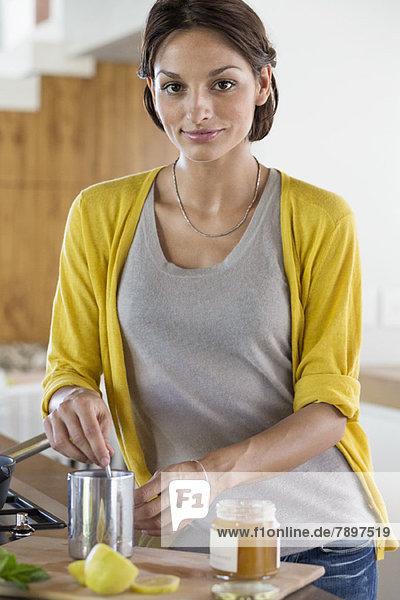 Frau beim Zubereiten von Kräutertee in der Küche