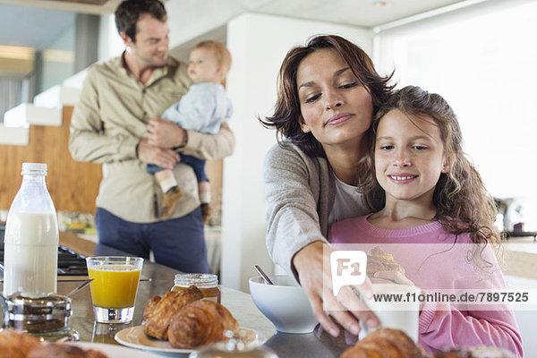 Mädchen frühstückt neben ihrer Mutter an der Küchentheke