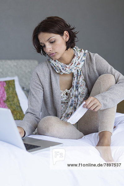 Woman working on a laptop with holding a paper on the bed