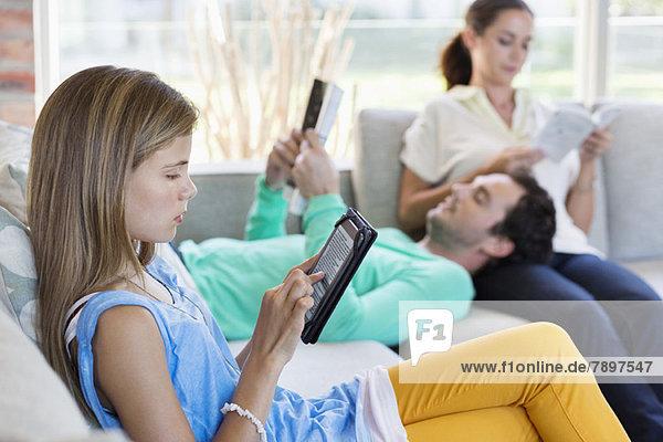 Mädchen  das ein digitales Tablett benutzt  während ihre Eltern zu Hause Bücher lesen.