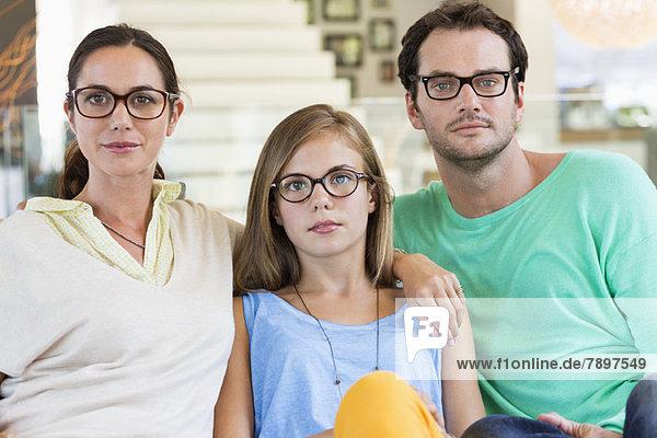 Porträt einer Familie  die auf einer Couch sitzt und eine Brille trägt.