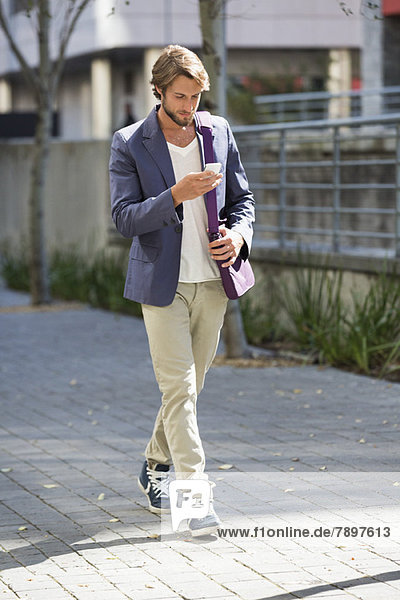 Man walking on a street reading text message