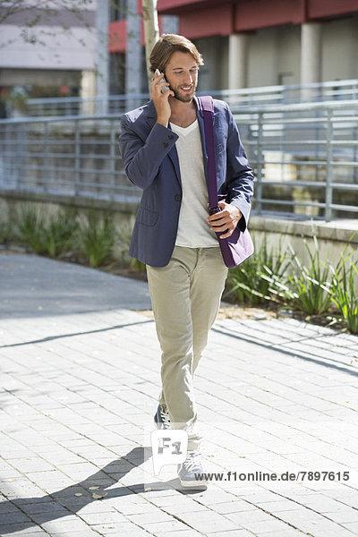 Mann  der auf der Straße geht und auf dem Handy spricht