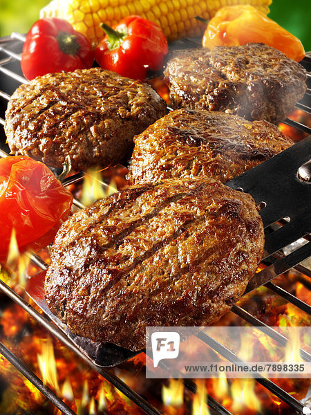 Beef burgers on a BBQ grill