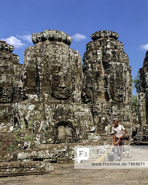 Bayon temple  man with broom working on the second terrace  face towers  smiling faces of Bodhisattva Lokeshvara  Avalokiteshvara