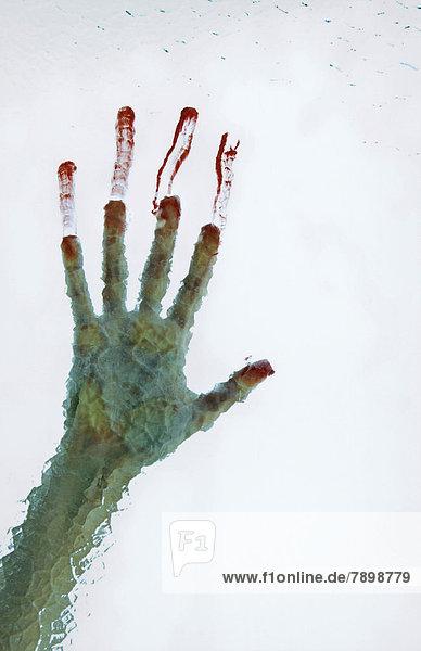 Blutige Hand rutscht Kathedralglasscheibe hinunter
