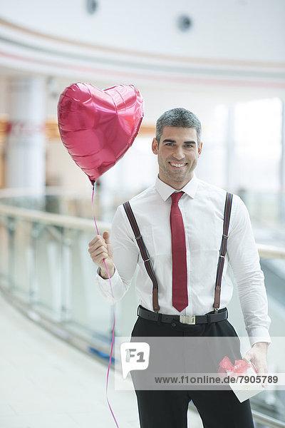 Geschenk  Geschäftsmann  Luftballon  Ballon  halten  Form  Formen  herzförmig  Herz