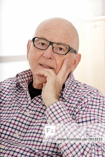 Senior Man head in chin wearing spectacles  thoughtful mood