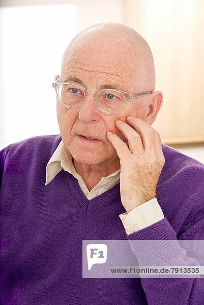 Senior man in a purple pullover and shirt  hand on cheek  wearing spectacles  in a thoughtful puzzled mood