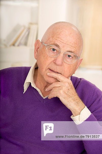 Senior Man in a purple pullover and shirt  finger in front of mouth  wearing spectacles  in a thoughtful puzzled mood