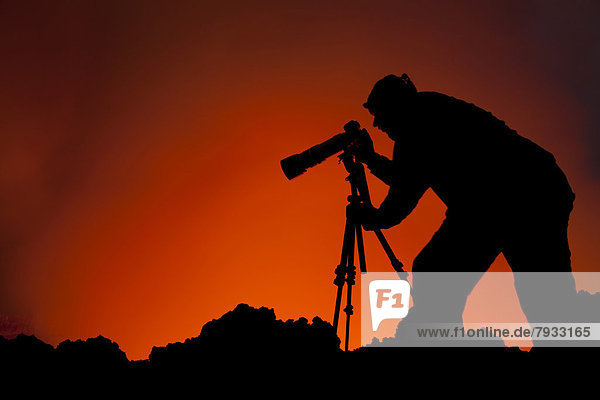 Photographer taking pictures at the lava lake in the crater of Mount Nyiragongo volcano