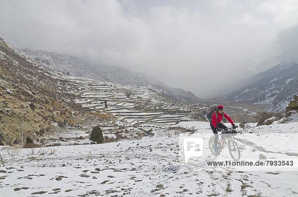 Radfahrer mit seinem Fahrrad im Schnee  auf dem Weg zum Thorong La Pass  5416 m