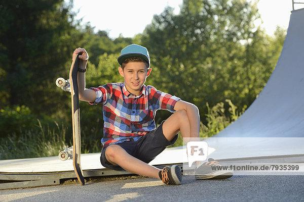 Boy with skateboard in a skatepark