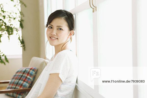 angelehnt  Frau  Fenster  lächeln  jung