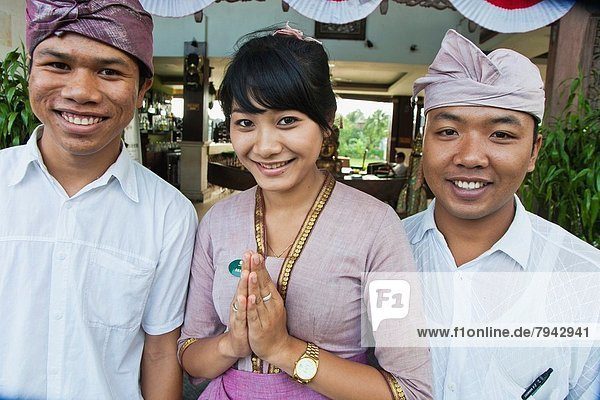 Portrait of two boys and a girl smiling and wearing traditional costumes. Ubud. Bali. Indonesia.