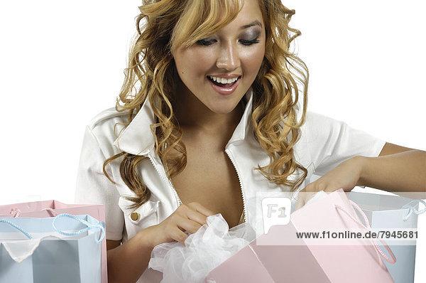 Junge Frau sieht in ihre Einkaufstüten  lächelnd