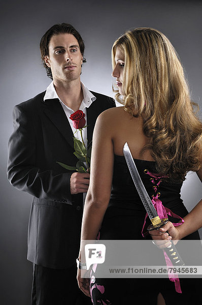 Young man holding a red rose standing in front of a woman holding a knife behind her back
