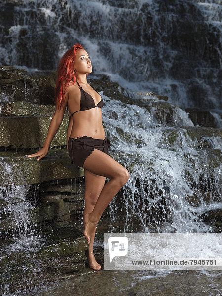 Junge Frau im Strand-Outfit neben Wasserkaskade
