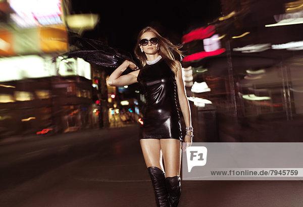 Junge Frau im sexy Outfit geht bei Nacht die Yonge Street hinunter