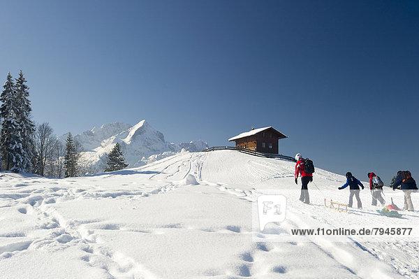 Schlittenfahrer und Holzhaus auf verschneitem Hügel  hinten die Alpspitze und Zugspitze Holzhaus