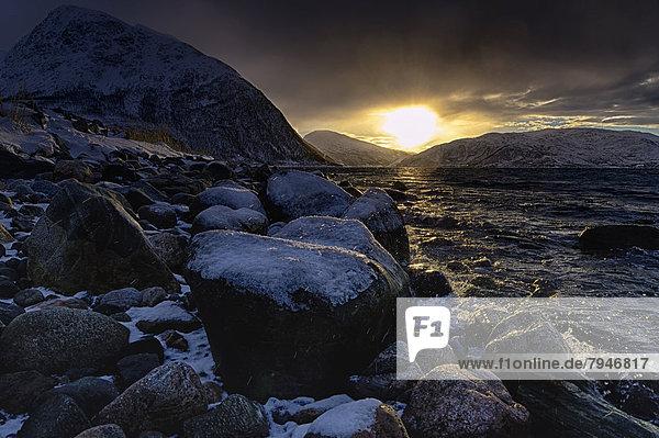 Steine mit Schnee an Fjordufer bei Sonnenaufgang