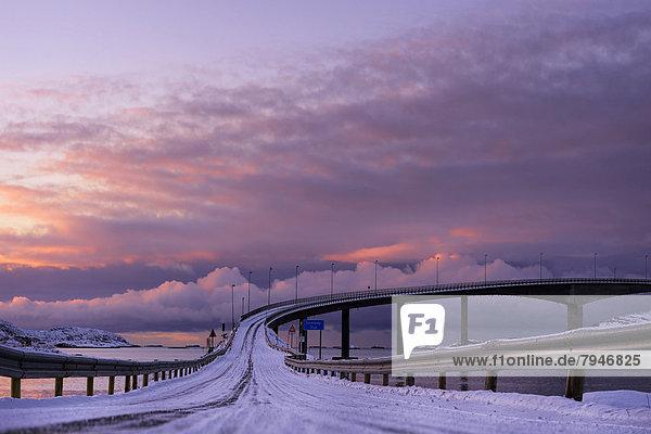 Brücke mit schneebedeckter Fahrbahn im Abendlicht