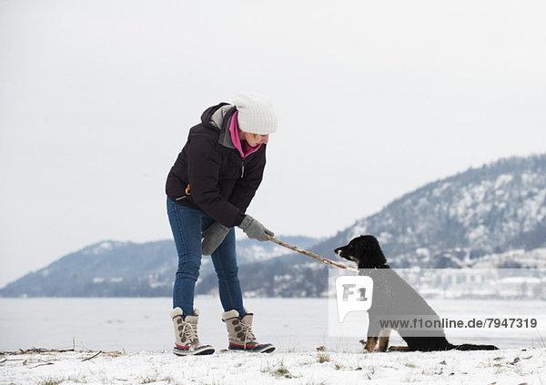 Volle Länge der jungen Frau  die den Stock am Hund hält  während sie auf einer verschneiten Landschaft steht.