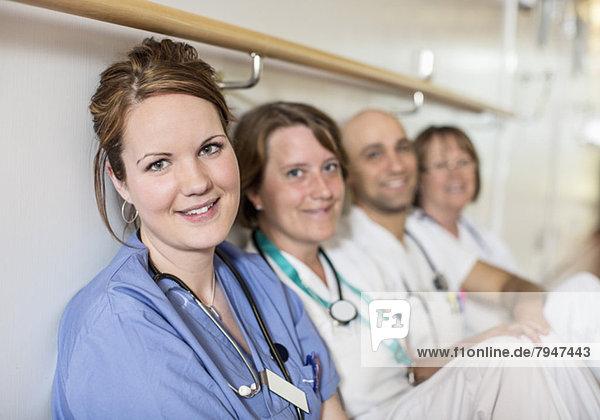Porträt einer schönen Ärztin mit Kollegen an der Wand im Krankenhaus