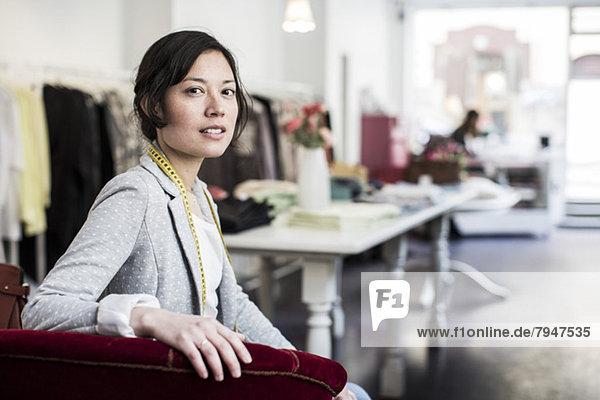 Porträt einer selbstbewussten Modedesignerin im Atelier