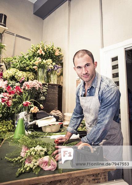 Porträt eines mittleren erwachsenen männlichen Floristen  der einen Blumenstrauß am Schreibtisch im Geschäft vorbereitet.