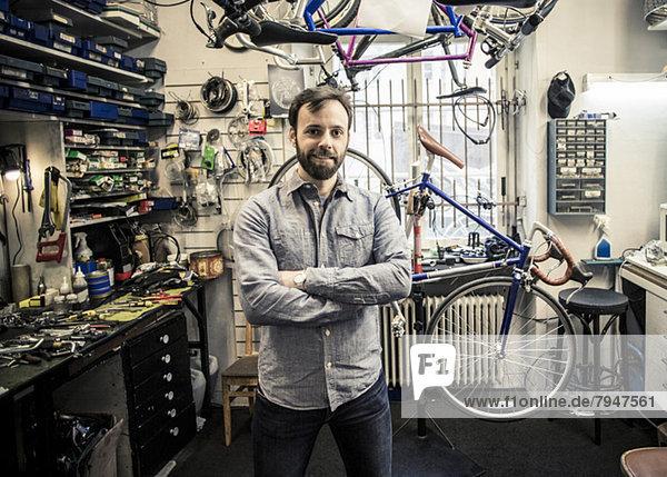 Porträt des mittleren erwachsenen männlichen Besitzers mit gekreuzten Armen in der Fahrradwerkstatt