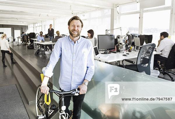 Porträt eines mittelständischen Geschäftsmannes  der mit Kollegen im Hintergrund im Büro Fahrrad hält