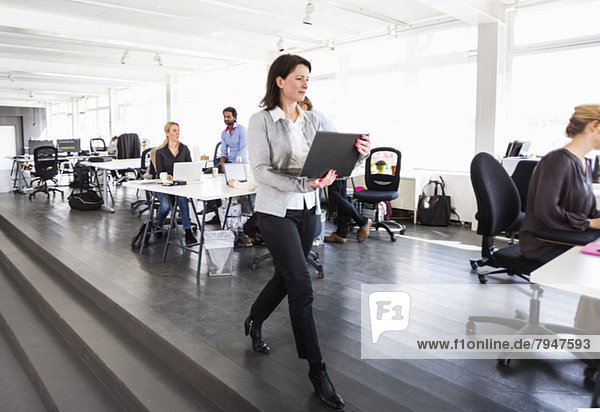 Mittlere erwachsene Geschäftsfrau mit Laptop im Büro