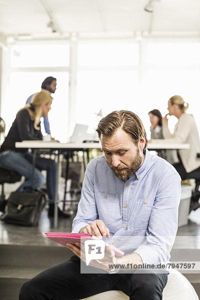 Mittlerer erwachsener Geschäftsmann mit digitalem Tablett und Kollegen im Hintergrund im Büro