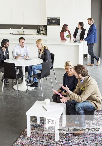 Blick aus der Vogelperspektive auf einen Geschäftskollegen  der in der Pause im Bürorestaurant diskutiert.