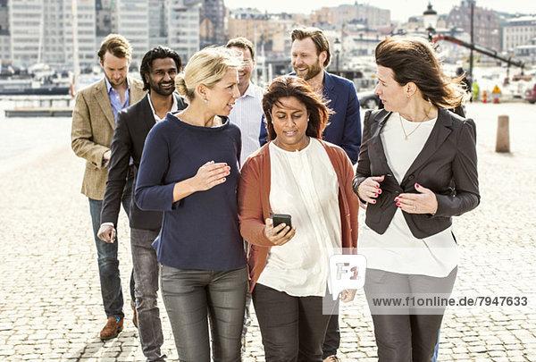 Geschäftsleute diskutieren beim Gehen auf der Straße