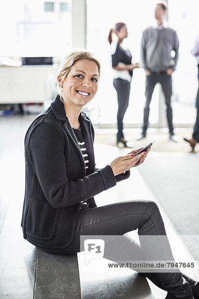 Porträt einer mittelgroßen Geschäftsfrau mit Handy auf der Treppe  während Kollegen im Hintergrund diskutieren.